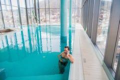 在豪华旅馆供以人员谈话在游泳池里面的手机 库存图片
