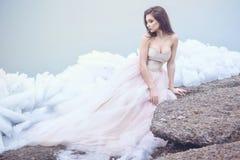 在豪华无背带的束腰舞会礼服的美好的模型坐残破的冰平板在有薄雾的海边 库存照片