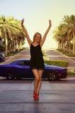 在豪华汽车附近的白肤金发的女孩 免版税库存图片