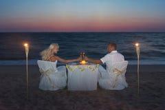 在豪华浪漫晚餐期间,与蜡烛,海上的夫妇靠岸 免版税库存照片