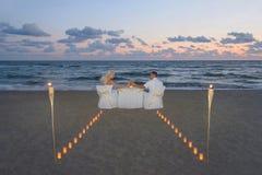在豪华浪漫晚餐期间,海上的夫妇靠岸 免版税图库摄影