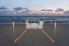 在豪华浪漫晚餐期间,海上的夫妇靠岸 免版税库存照片