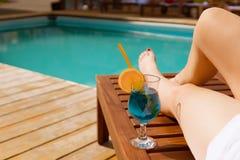 在豪华游泳池附近的松弛妇女 库存照片
