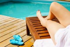 在豪华游泳池附近的松弛妇女 免版税库存图片