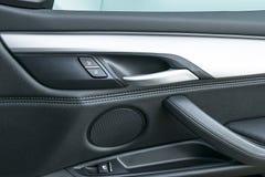 在豪华现代汽车里面的车门把柄有黑皮革和开关按钮控制的,现代汽车内部细节 免版税图库摄影