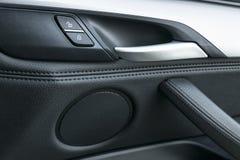 在豪华现代汽车里面的车门把柄有黑皮革和开关按钮控制的,现代汽车内部细节 免版税库存照片