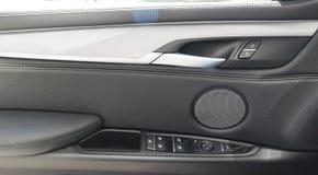 在豪华现代汽车里面的车门把柄有黑皮革的和开关按钮控制现代汽车内部细节 免版税库存照片
