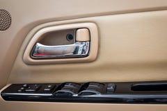 在豪华现代汽车里面的门把手在开关按钮 图库摄影