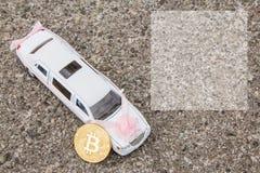 在豪华白色汽车附近模型的Bitcoin金黄硬币在沥青背景的 婚礼, Bitcoin接受了和财政 免版税图库摄影