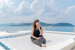 在豪华yacth的亚洲美丽的妇女画象在海和b 图库摄影