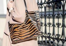 在豹子印刷品特写镜头的袋子 大购物的皮革提包在女性手上 走在城市的妇女 一件米黄外套的女孩 免版税库存照片