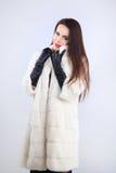 在貂皮皮大衣的有吸引力的模型在白色背景 免版税库存图片