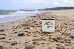 在贝加尔湖含沙岸的小卵石的上釉的阵营杯子在波浪期间的在山背景在夏天 免版税库存照片