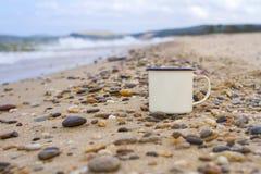 在贝加尔湖含沙岸的小卵石的上釉的阵营杯子在波浪期间的在山背景在夏天 免版税库存图片