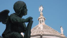 在贝加莫,在前景的古铜色天使洗礼池的天使雕象  股票录像