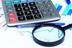 在财务图表的放大镜 图库摄影