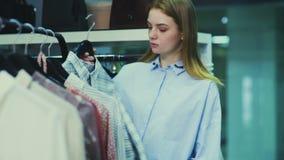 在购物中心的妇女购物 站立在与选择套头衫的衣裳的架子附近 采摘方格的衬衣 股票视频