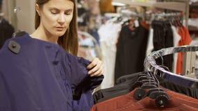 在购物中心的少妇购物 与选择夹克的衣裳的常设近的架子 拾起蓝色外套 股票录像