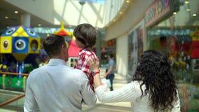 在购物中心的愉快的家庭圣诞节购物 有母亲和父亲的男孩 父母和孩子有包裹的与 股票视频