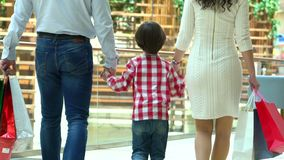 在购物中心的愉快的家庭圣诞节购物 男孩握一只手母亲和父亲 父母和孩子有包裹的 股票视频