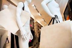 在购物中心的购物,时装模特站立与包裹购物 免版税库存照片