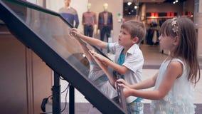 在购物中心,小孩子朋友用途交互式触摸屏幕显示的现代技术对于查寻信息 影视素材