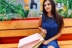 在购物的女孩在街道,拿着纸袋的妇女的画象上以后,在商店附近 免版税库存照片