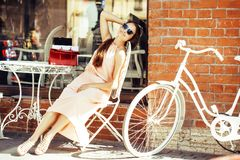 在购物的年轻俏丽的深色的妇女在咖啡馆以后外面坐街道微笑 免版税库存照片
