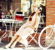 在购物的年轻俏丽的深色的妇女在咖啡馆以后外面坐街道微笑 库存图片