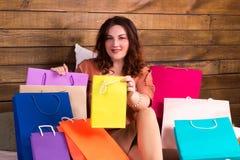 在购物的愉快的妇女与在床上的五颜六色的纸袋以后 免版税库存照片