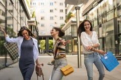 在购物的漫步的城市街道以后的妇女 获得乐趣 免版税库存照片