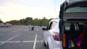 在购物的被投入的袋子以后的两名愉快的妇女在汽车的后车箱,在它坐并且准备好驾驶  股票录像