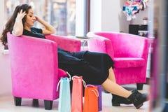 在购物袋围拢的椅子的女性开会 免版税库存图片