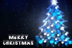 在贺卡的圣诞快乐愿望与从蓝色光的圣诞树剪影 免版税图库摄影