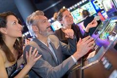 在赌博娱乐场激动观看老虎机的人 图库摄影