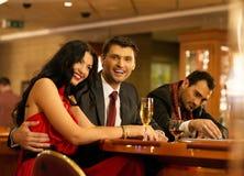在赌博的桌后的愉快的青年人 免版税库存照片