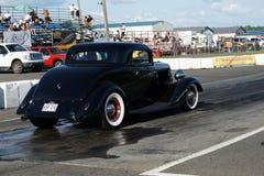 在赛马跑道的旧车改装的高速马力汽车 图库摄影