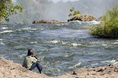 在赞比西河边的非洲儿童设置在维多利亚瀑布,利文斯东,赞比亚顶部 免版税库存图片