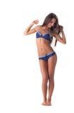 在赤足摆在蓝色镶边的比基尼泳装的逗人喜爱的模型 免版税库存照片