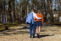 在走在公园的爱的愉快的年轻夫妇在秋天 库存照片