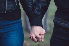 在走在公园的爱的年轻夫妇握手 免版税图库摄影