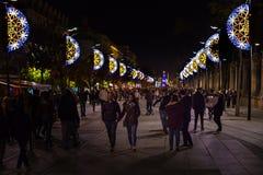 在走在圣诞节期间的塞维利亚街道和许多的圣诞灯装饰人 库存图片