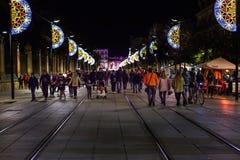 在走在圣诞节期间的塞维利亚街道和许多的圣诞灯装饰人 免版税库存照片