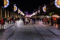 在走在圣诞节期间的塞维利亚街道和许多的圣诞灯装饰人 库存照片