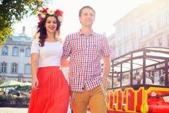 在走在城市的爱的愉快的夫妇握手 免版税库存图片