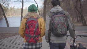 在走在有背包的公园的年轻游人的背面图在他们的后面 人带领自行车和妇女  影视素材
