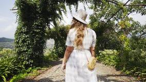 在走在有藤植物的胡同的女孩之后在小山之间 股票视频