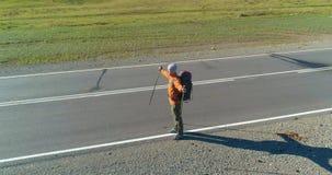 在走在柏油路的旅行者游人的飞行 巨大的农村谷夏日 远足人的背包 股票视频