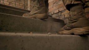 在走在楼上在砖背景,被伪装的人的官员起动的特写镜头脚室内 股票录像