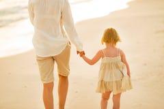 在走在海滩的母亲和女婴的特写镜头 免版税库存图片